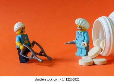 Lego minifigures of patient with broken leg and head buying drugs from doctor to get better. Editorial image isolated on orange background, macro photography, close up photo. Concept of healthcare