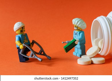 Lego minifigures of patient buying painkiller drugs from doctor or bribing doctor for prescription. Editorial image, close up photo isolated on orange background, macro photography, studio shot.