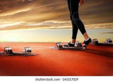 Legs of athlete on start line of running track on sunset background