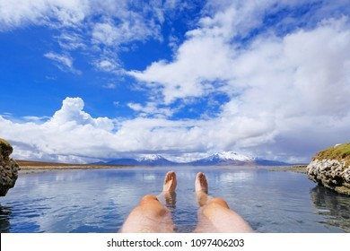 The legs of an athletic man in natural thermal hot spring Polloquere, Salar De Surire salt lake, Isluga Volcano National Park, Chile, South America