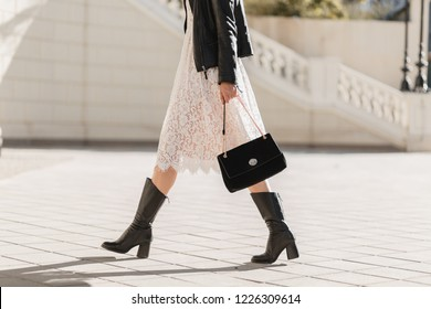 legs of attractive woman walking in street in high leather boots, fashionable outfit, holding purse, black leather jacket and white lace dress, spring autumn style, shoes fashion trend
