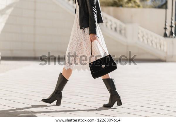 高い革のブーツを履いて通りを歩く魅力的な女性の脚、ファッショナブルな服装、持ち物、財布、黒い革のジャケット、白いレースのドレス、春の秋のスタイル、靴の流行