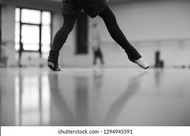 Legs of ballerina dancing in pointe in warm socks at rehearsal in the hall