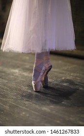 The legs of the ballerina in pointe standing in the rehearsal hall of the theater