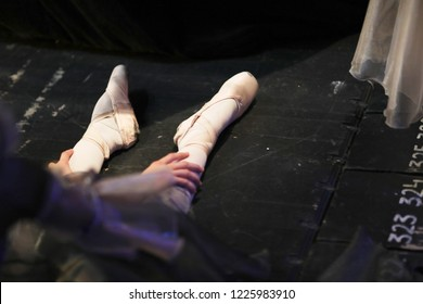 The legs of a ballerina sitting on the floor of the stage behind the curtains of the theater during the intermission of the performance