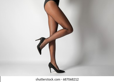 40223d64796 Legs of beautiful young woman in black tights on light background