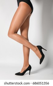 Legs of beautiful young woman in tights on light background