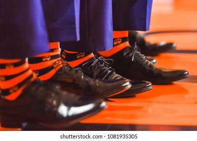 Legs with black shoes and orange socks.