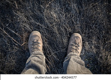 Legs in boots standing on burnt withered grass, outdoors