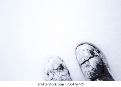 Legs in boots standing on a snow white field