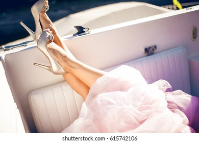 legs of the bride in beige shoes, beautiful bride showing off sexy legs