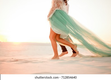Legs of bride and groom walking barefoot on sand in desert at sunset. Close up.