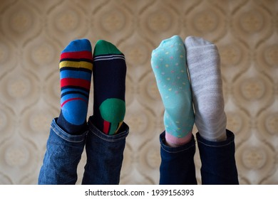 Legs in bright funny different socks are raised up. March 21, world down syndrome day
