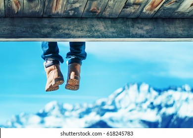 Legs in brown shoes hanging from a wooden bridge against a background of mountains and blue sky