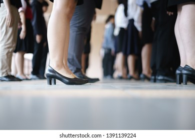 Legs of business man and woman waiting in a row for job interview or taking an exam