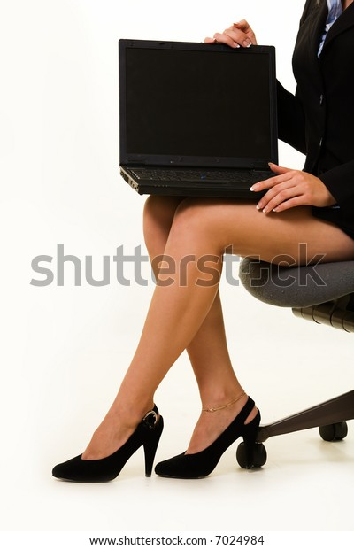 Legs of business woman sitting on a stool holding a laptop computer on her lap