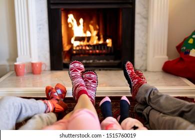 Les jambes d'une famille caucasienne allongée sur le sol, un couple avec leur jeune fils et leur fille se réchauffant les pieds ensemble devant une cheminée dans leur salon à l'heure de Noël