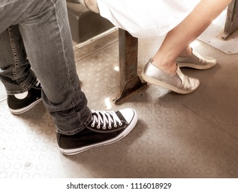 legs of a Caucasian woman in slippers without heels and men in jeans and sneakers sitting in public transport
