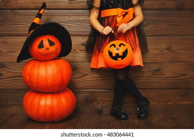 legs of  child girl in witch costume for Halloween with pumpkin Jack on a dark wooden background