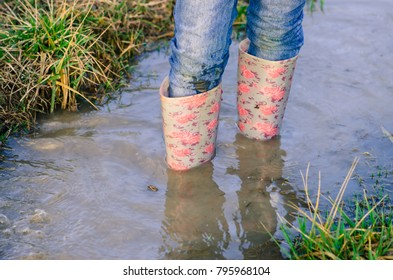 legs of child in pink rubber boots standing in water puddle