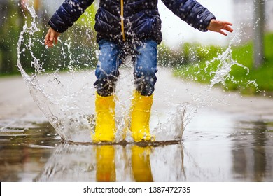 legs of child with rubber boots jump in puddle on an autumn walk