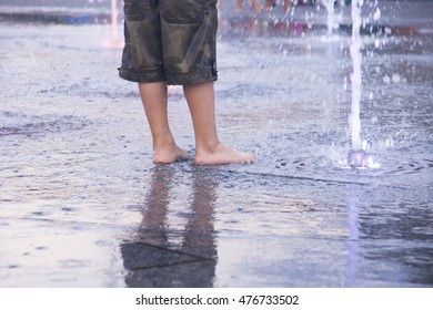 legs of children having fun with fountain shot during summer time