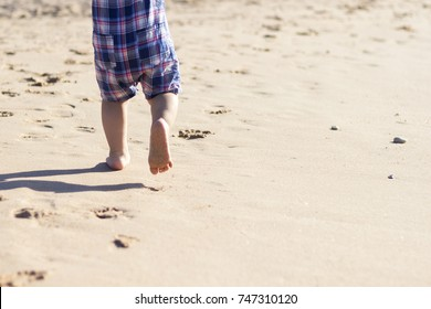 Legs of children stand on the beach. Baby feet in the sand. Summer beach background. Summertime holidays concept. Copy space.