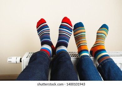 legs with colorful socks on heating radiator
