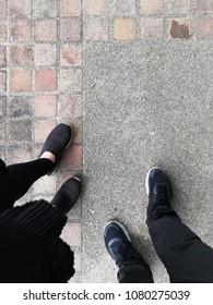 legs of couple walking on road