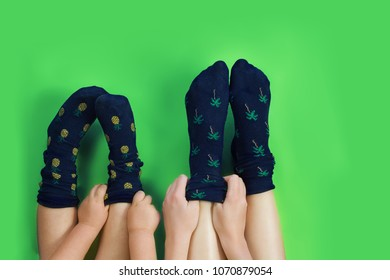 Legs with cute blue socks on green background.