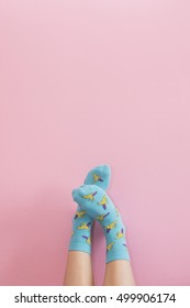 Legs with cute blue socks on pink wall. Minimalism fashionable winter set.