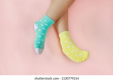 Legs with cute pastel green and yellow socks on pink background. Minimalism fashionable winter set.