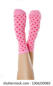 Legs with cute pink socks on white background. Minimalism fashionable winter set
