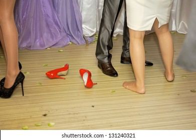 legs of dancing young people and red shoes