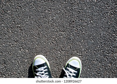 Legs in dark trainers shoes standing on asphalt texture, road texture, top view.