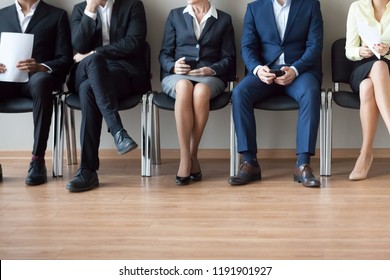 Legs of diverse job applicants sitting on office chairs in corridor waiting in turn for interview, feet of work candidates expect in queue for hiring or employment talk. Recruitment concept
