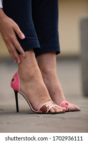 Legs in elegant shoes  of beautiful young woman standing on the street against plain wall, no brand, copy space,