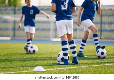 Legs of european football boys kicking balls on field. Group of young football players on soccer training. Football practice training background
