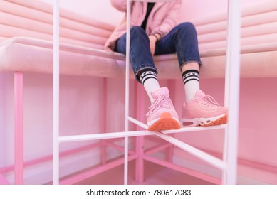 The legs of a fashionable girl in pink sneakers, which sits on a pink sofa. Street fashion.
