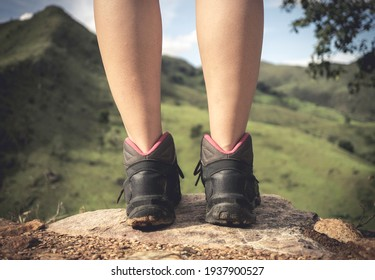 legs and feet of an adventurer girl  on the top of a stone looking at the horizon