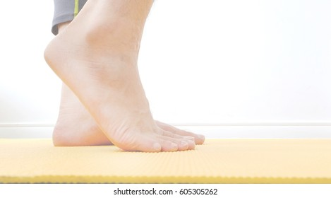 legs and feet of a beautiful woman walk on a yellow yoga mat as the body swells and stretches the muscles before exercise.Health and Sports Concepts