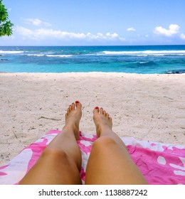 Legs and feet with fake spray tan and painted toenails on sun lounger on tropical beach with pink towel at Lefaga, Upolu Island, Western Samoa, South Pacific