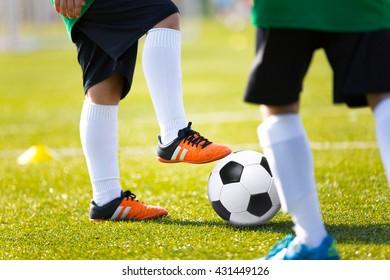 Legs feet of football player in white sports socks orange shoe and green shirt kicking soccer ball. Training session on green fresh grass for youth football soccer team.
