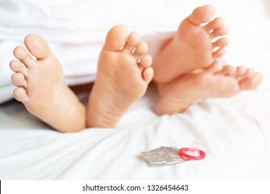 legs feet of two Lovers sleeping side by side embracing under blanket sheets. passion couple having sex. with lust and making love while having activity time, condom on the bed. Contraception concept