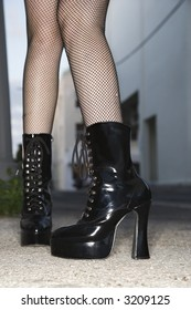 Legs and feet wearing high heeled boots of Caucasian young woman in urban setting.