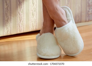 Legs and feet in white fluffy fur home slippers resting in the livingroom in a sunday light