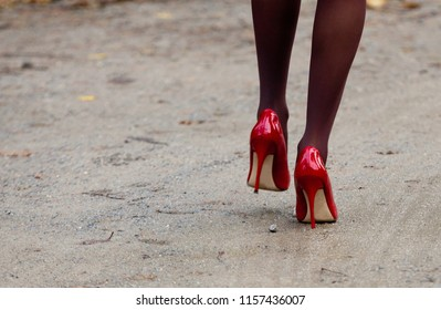 legs and feet of a woman with red high heels, going away