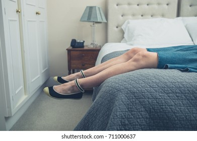 The legs and feet of a young woman relaxing on a bed