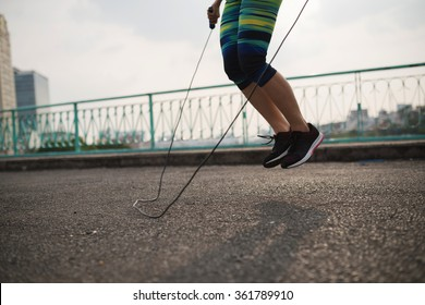Legs of female athlete with jump rope training outdoors