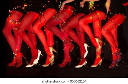 Legs of female cabaret dancers with christmas lights tied around body in red leggings and high heels shoes on dark background